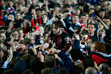 BOURNEMOUTH, ENGLAND - APRIL 27:  Harry Arter of Bournemouth celebrates victory with fans as they invade the pitch after the Sky Bet Championship match between AFC Bournemouth and Bolton Wanderers at Goldsands Stadium on April 27, 2015 in Bournemouth, England. Bournemouth's 3-0 victory puts them on the brink of promotion to the Barclays Premier League.  (Photo by Clive Rose/Getty Images)