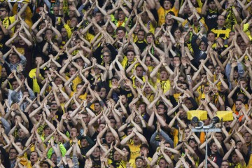 Supporters of Borussia Dortmund cheer during their German first division Bundesliga soccer match against Bayern Munich in Dortmund